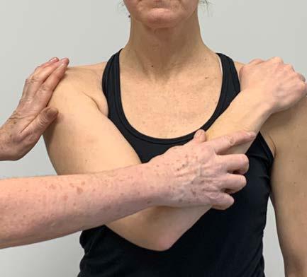 Bilden visar hur undersökningen cross-body test utförs.